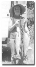 Photo of wife Pauline St. Onge holding two fish.