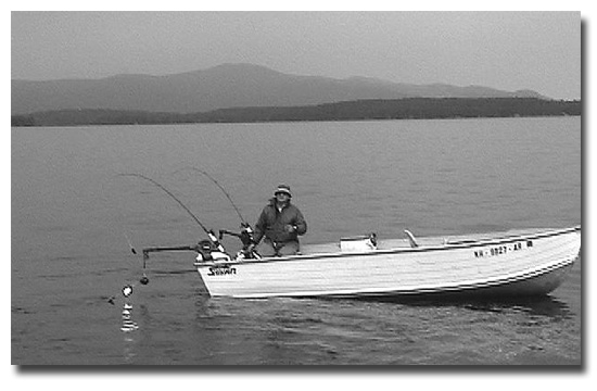 """Ted St. Onge trolling with Osippee Mountains in the background. You can see the Dave Davis spinners attached to the downrigger ball on this side of the boat. He uses them as an attractor and has his release device 18"""" above them on the cable with his sewn shiner spinning slowly just behind the Davis spinners and he always catches salmon and trout with this rig."""