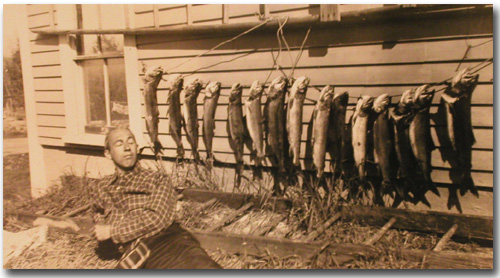 Uncle Gordon Hines, cooling it, with a big string of lake trout.