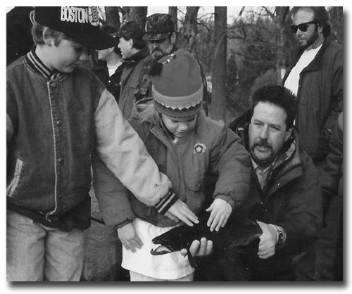 Steve Perry showing children large male salmon before stripping him of milt.